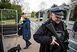 © London News Pictures. 22/04/2016. London, UK. An armed police officer walks past a dog walker next to security barriers. Heightened security surrounding the residence of the US Ambassador to the United Kingdom in Regents Park, London, where the President of the United States Barak Obama is staying during his visit to the UK. Photo credit: Ben Cawthra/LNP