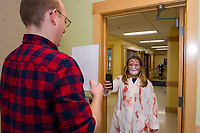 Delaney Sleeper reads a poem held by Youth Librarian John Locke while she walks backwards to see the reflection of your future mate during the Tween/Teen Halloween party at the Meredith Community Center on Tuesday.  Karen Bobotas for the Laconia Daily Sun