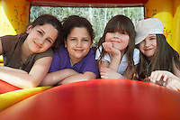Four girls (7-12) lying in row in bouncy castle portrait