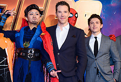 Benedict Cumberbatch (centre) and Tom Holland (right) pose with a Marvel cosplayer attending the Avengers: Infinity War UK Fan Event held at Television Studios in White City, London.