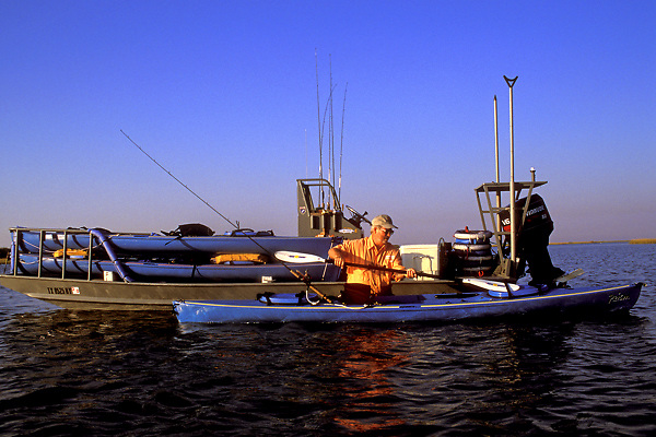Stock photo of a man standing in the water and loading his kayak with supplies for fishing