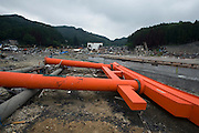 A red torii gate from a Shinto Shrine lies among the debris that once also included a pleasure boat that has been tossed atop the building center right  by the March 11 mega tsunamis in Otsuchi, Iwate Prefecture, Japan on 12 June, 2011. Photographer: Robert Gilhooly
