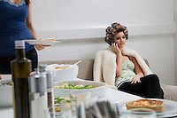 Model in Curlers on Cell Phone Near Lunch Buffet