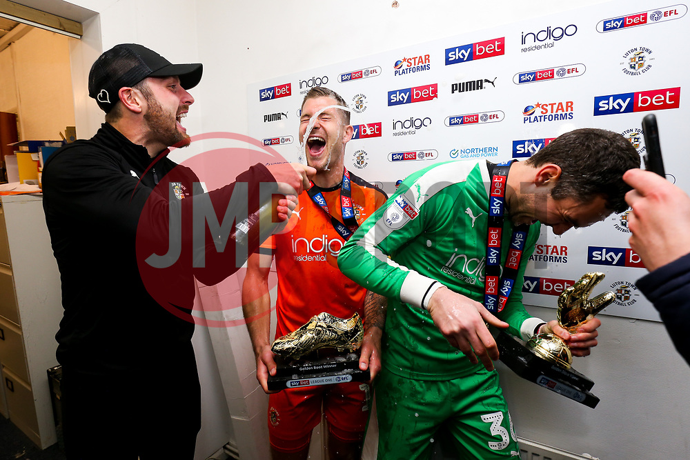 Danny Hylton sprays champagne as James Collins and James Shea of Luton Town win the 2018/19 Sky Bet League One Golden Boot and Golden Glove awards as Luton Town celebrate winning the league and securing automatic promotion from Sky Bet League 1 to the Sky Bet Championship - Rogan/JMP - 04/05/2019 - Kenilworth Road - Luton, England - Luton Town v Oxford United - Sky Bet League One.