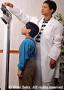 Medical African American Nurse Weights Hispanic Boy at Urban Clinic