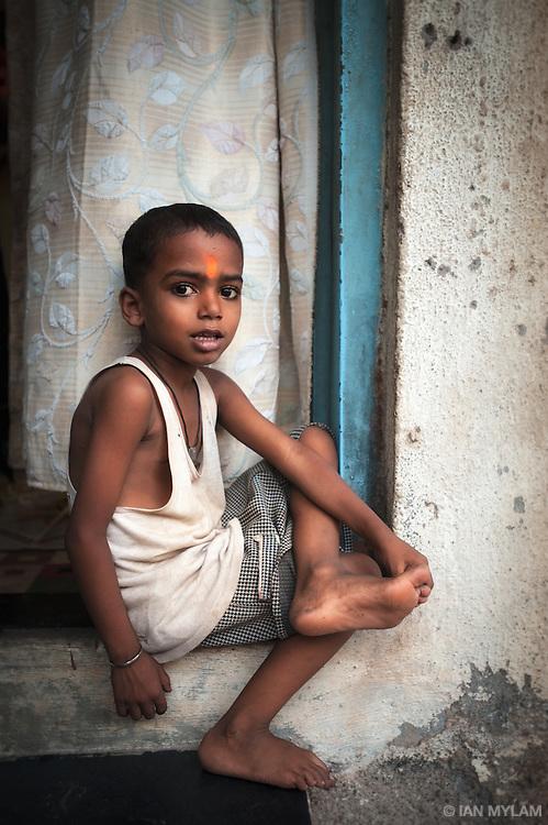 Boy Sitting in an Open Window - Dharavi, Mumbai, India