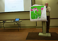 Geologist Kevin Hill holds up a map at a meeting for the community set up by Texas Brine to ask the community for permission for access to their properties so they can set up sensors for seismic testing. The state has required Texas Brine to produce a seismic map of the area to get a clear picture of what the salt mine looks like now.