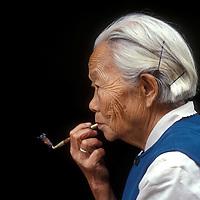 China, Hubei Province, Wushan, Tian Yu Qun smokes her pipe at home by Dragons Gate Bridge near Three Gorges Dam