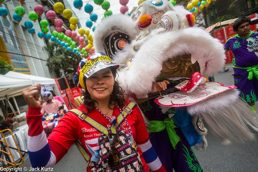 01 FEBRUARY 2014 - BANGKOK, THAILAND:  An anti-government protestor walks down Yaowarat Road with a Lion Dancer during a protest in the Chinatown section of Bangkok. The anti-government protest movement, led by the People's Democratic Reform Committee (PDRC) organized a march through the Chinatown district of Bangkok Saturday and disrupted the city's famous Chinese New Year festival. Some streets were blocked and protest leader Suthep Thaugsuban walked through the neighborhood collecting money. The march was in advance of massive protests the PDRC has promised for Sunday, Feb. 2 in an effort to block Thais from voting in the national election.    PHOTO BY JACK KURTZ