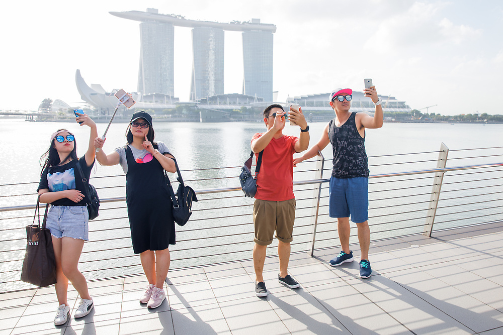 Tourists take photographs of themselves in front of Marina Bay Sands while standing on the Jubilee Bridge, Singapore.