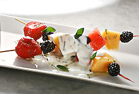 Fruit kebab on a white plate: Blackberry, strawberry, cantaloupe, watermelon, sauced with a mix of youghurt ,caramel and mint on top.