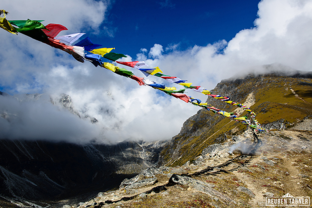 Preyer flags and smoke from incence blow in the wind above the village of Machermo, Sagarmatha National Park, Nepal.