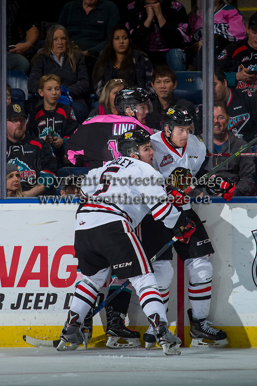 KELOWNA, CANADA - OCTOBER 21: Alex Overhardt #17 and Matthew Quigley #5 of the Portland Winterhawks check Kole Lind #16 of the Kelowna Rockets into the boards on October 21, 2017 at Prospera Place in Kelowna, British Columbia, Canada.  (Photo by Marissa Baecker/Shoot the Breeze)  *** Local Caption ***