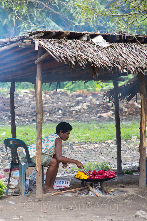 Woman frying food at a market in Lae, Papua New Guinea
