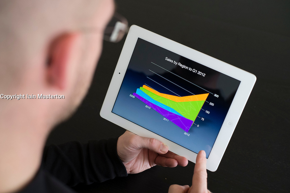Man preparing business presentation with charts on iPad3 tablet computer