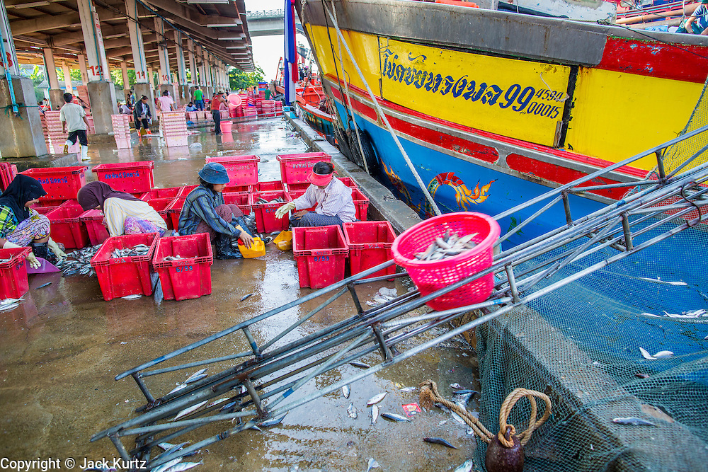 30 OCTOBER 2012 - PATTANI, PATTANI, THAILAND: A bucket fish comes off a fishing trawler while Thai Muslim workers sort and grade fish in the port of Pattani, province of Pattani, Thailand. Thailand's fishing industry relies on immigrant workers, mostly from Myanmar but also Laos and Cambodia. There have been allegations of worker abuse, including charges that workers are held in slave labor like conditions. There are hundreds of thousands of immigrant workers in the Thai fishing industry. Most are from Myanmar (Burma) but there are also Cambodian and Laotian workers in the industry.    PHOTO BY JACK KURTZ