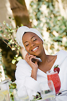 Woman in bathrobe using mobile phone