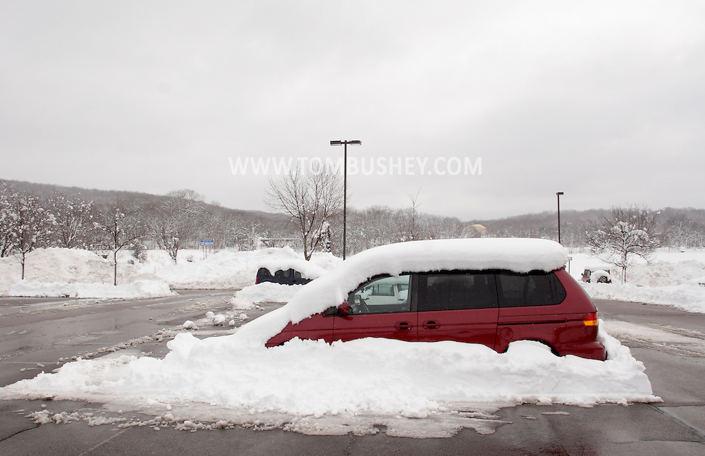 Monroe, New York - A van is covered in snow in a commuter parking lot the morning after a storm dropped 31 inches of snow and a plow cleared the lot around the vehicle. Feb. 27, 2010.
