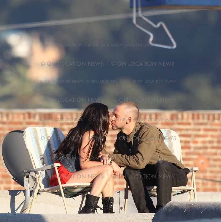 """July 23rd 2010  Los Angeles, CA.  ***EXCLUSIVE*** Megan Fox and Dominic Monaghan share some Vodka and a passionate kiss while sitting on lawn chairs on the rooftop of a Liquor store in a gritty  Los Angeles neighborhood. Fox and Monaghan spent the day filming scenes together for their starring roles in Eminem and Rihanna's music video for """"The Way You Lie"""".  Megan and Dominic also filmed a scene inside the liquor store as well as inside  a run down dive bar next door. Photo by Eric Ford/ On Location News 818-613-3955"""