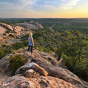 Female hiker is watching sunrise at Enchanted Rock State Park, Texas.