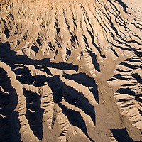 USA, Utah, Caineville, Eroded cliffs of North Caineville Mesa above Fremont River on autumn evening