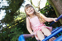 Girl Sitting on monkey bars in backyard portrait