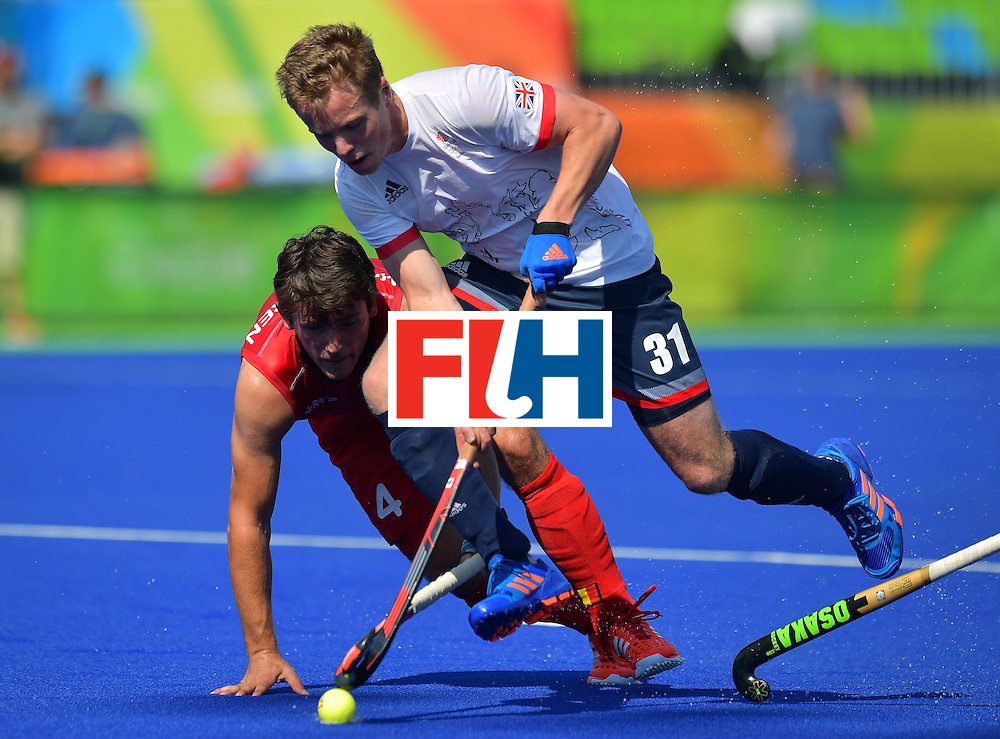Belgium's Arthur van Doren (L) fights for the ball with Britain's Ian Sloan during the men's field hockey Belgium vs Britain match of the Rio 2016 Olympics Games at the Olympic Hockey Centre in Rio de Janeiro on August, 6 2016. / AFP / Carl DE SOUZA        (Photo credit should read CARL DE SOUZA/AFP/Getty Images)
