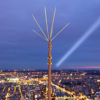France, Paris, Spotlight glows in evening sky above lightning road from top of Eiffel Tower