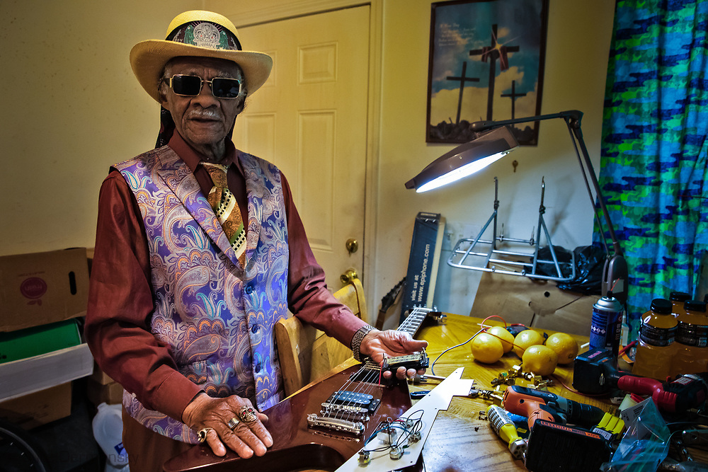 Little Freddie King, a famous New Orleans based blues musican  working converting an inexspessive guitar into a specialzed blues insturament.  KIng has a large collection of guitars that he specialized in a way that amps up the sound.  He uses his kitchen in a home in New Orleans Musicain Village, created after ktraina to house muscieans as his workshop.