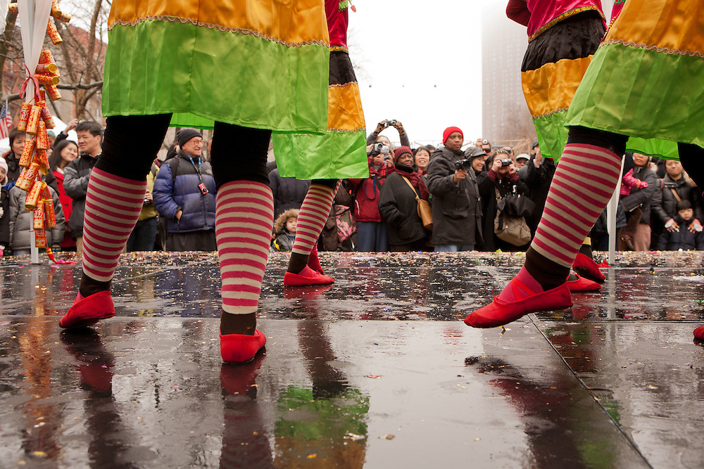 Traditional dancers on stage in the drizzle, celebrating the Year of the Dragon.