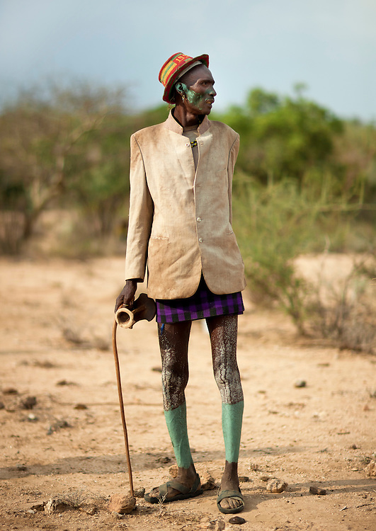 Hamer man with ceremony costume,  wooden stick and headrest in his hand. Omo valley, Ethiopia.