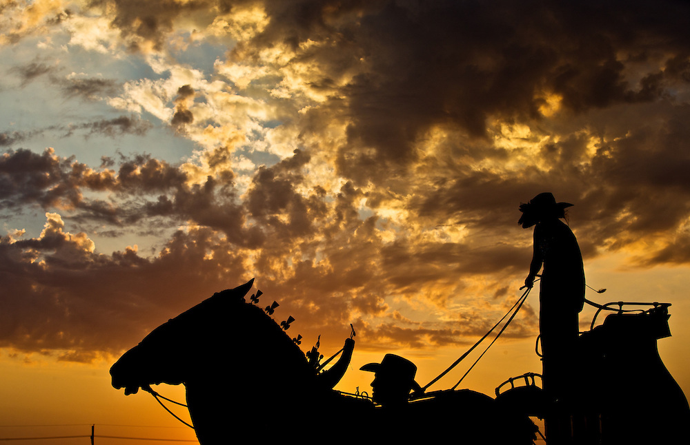 The Mark Messenger Memorial Hitch is silhouetted against a sunset during the Draft Horse Hitch Show Friday evening outside the Five Points Bank Arena at the Nebraska State Fair in Grand Island. (Independent/Matt Dixon)