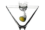 Single green olive splashing into Martini glass. A studio shot by product photographer Jonathan Bowcott