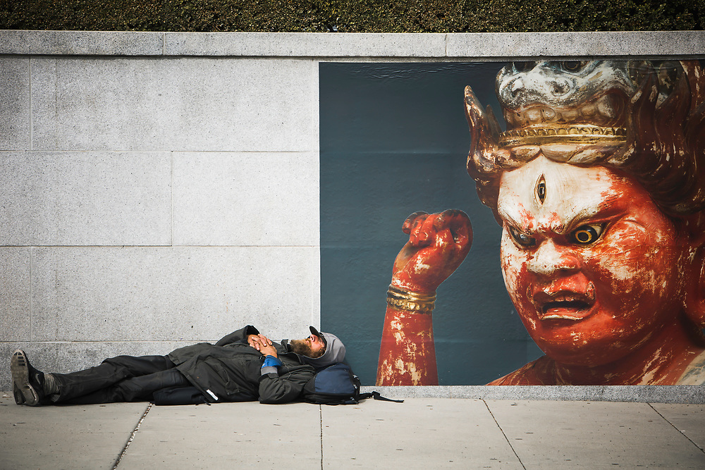 Man takes a nap near Civic Center at March for Our Lives 2018 demonstration in San Francisco, CA. Copyright 2018 Reid McNally.