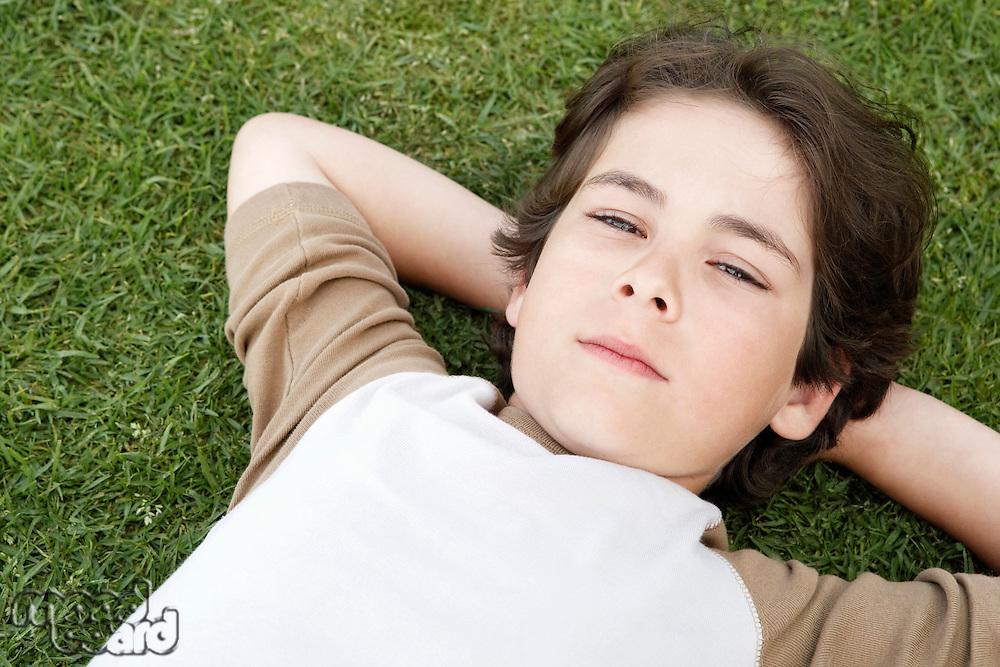 Pre-teen boy lying on back in grass hands behind head elevated view