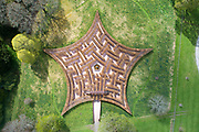 Aerial view of the Murray star shaped maze, designed by Adrian Fisher, in the grounds of Scone Palace, rebuilt 1802-12 by William Atkinson in late Georgian Gothic style, Perthshire, Scotland. The maze is planted with copper and green beech, after the Earl of Mansfield's family tartan, Ancient Murray of Tullibardine, and is in the shape of a 5 pointed star from the Murray emblem. There was originally a church, then priory, then abbey on this site before it became a home. The palace is now open to the public. Picture by Manuel Cohen