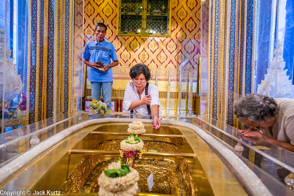"22 JULY 2013 - PHRA PHUTTHABAT, THAILAND:  People pray at the footprint of Buddha in the Mondop (chapel that houses the footprint) before the Tak Bat Dok Mai at Wat Phra Phutthabat in Saraburi province of Thailand, Monday, July 22. Wat Phra Phutthabat is famous for the way it marks the beginning of Vassa, the three-month annual retreat observed by Theravada monks and nuns. The temple is highly revered in Thailand because it houses a footstep of the Buddha. On the first day of Vassa (or Buddhist Lent) people come to the temple to ""make merit"" and present the monks there with dancing lady ginger flowers, which only bloom in the weeks leading up Vassa. They also present monks with candles and wash their feet. During Vassa, monks and nuns remain inside monasteries and temple grounds, devoting their time to intensive meditation and study. Laypeople support the monastic sangha by bringing food, candles and other offerings to temples. Laypeople also often observe Vassa by giving up something, such as smoking or eating meat. For this reason, westerners sometimes call Vassa the ""Buddhist Lent.""    PHOTO BY JACK KURTZ"