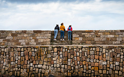 Women on harbour wall looking at view in St Andrews, Fife, Scotland, UK