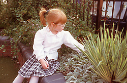 Young girl with visual impairment touching plants in tactile garden,