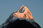 Red light gently graces the snow-covered Mitre Peak, Fiordland National Park, New Zealand