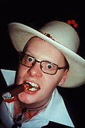 Wide-eyed man wearing white cowboy hat chewing on chunky cigar, Hellfire club, London, U.K, 2000.