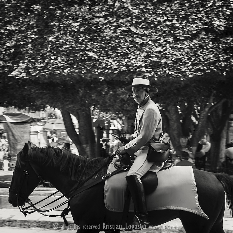 Police man on horse back, dressed in old style traditional costume