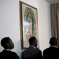 "Sudanese refugees pray during a mass in a house inmprovised into a church  on February 27 2011. The municipality hung 1,500 red flags around the city as a sign of warning and put up hundreds of banners reading: ""Protecting our home, the residents of Eilat are drawing the line on infiltration."" Eilat Mayor Meir Yitzhak Halevi said that 10 percent of the city's population was currently made up of migrants and that the residents feel that the city has been conquered...Photo by Olivier Fitoussi."