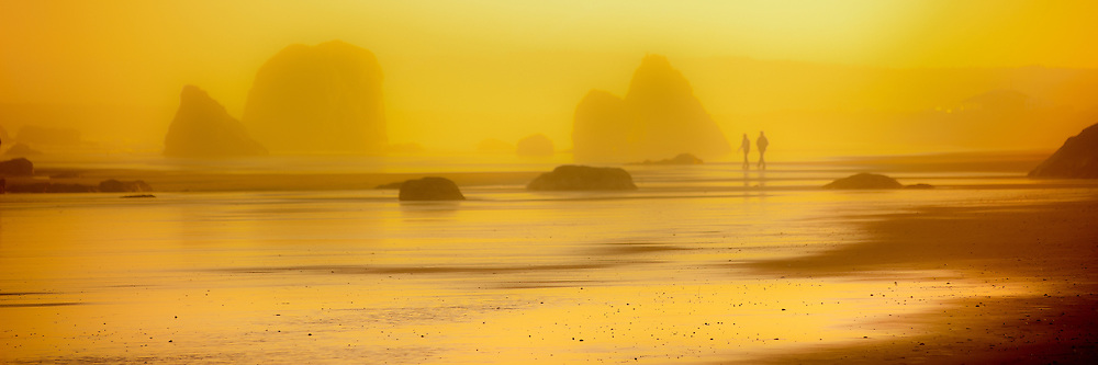 A couple walks along the beach in a foggy sunrise at Bandon Beach, Oregon