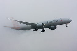 "January 3rd 2015, Heathrow Airport, London. Low cloud and rain provide ideal conditions to observe wake vortexes and ""fluffing"" as moisture condenses over the wings of landing aircraft. With the runway visible only at the last minute, several planes had to perform a ""go-round"", abandoning their first attempts to land. PICTURED: Water streaming from its wings, an A merican Airlines Boeing 777 prepares to land on Heathrow's runway 27L."