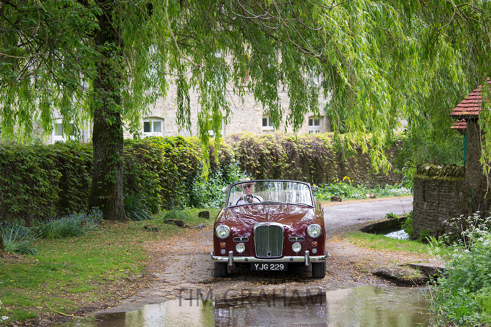 Motorist driving 1961 British made Alvis TD21 DHC drophead ooupe classic car through a ford on country lane in The Cotswolds, England