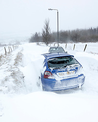© London News Pictures. 23/03/2013 . Blizzards cause huge snow drifts which cover cars on a road in Hadfield, Derbyshire. The UK has been hit by heavy snow and flood alerts. Photo credit: Duncan Fawkes/LNP