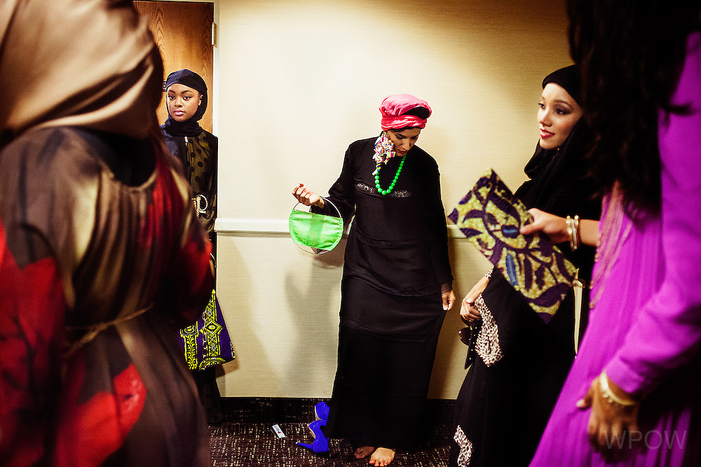 Lily Monir Matini, center, gets into wardrobe backstage during a fashion show hosted by Reaching All HIV+ Muslims in America (RAHMA) in Washington, DC on Aut. 16, 2014. The clothing and accessories are all made by Muslim women designers from around the US, specializing in creating modest fashion that complies with Islamic tradition. (photo by Lindsey Leger)