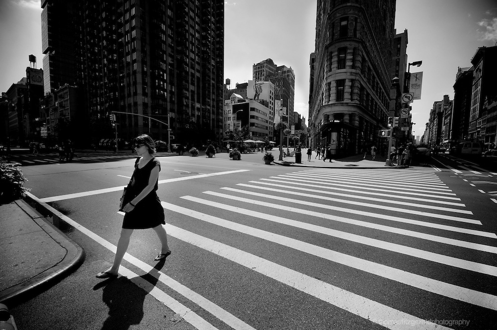 A Woman crosses at a cross walk in front of the iconic Flat Iron Building
