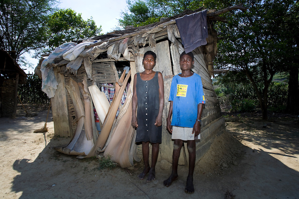 A woman and her teenage son stand in front of their home.